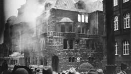 A group of men look at smoke billowing out of the synagogue in Essen, Germany, burned during Kristallnacht.