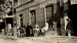 Photograph of children playing on the sidewalk as women look on while they sit on the step of a nearby building.