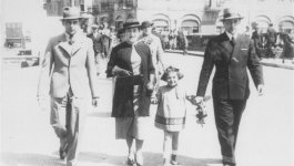 A group of three adults and a little girl walk down the street toward the camera. A group of people walk in the background.