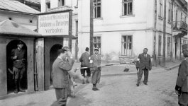 Street in the Stanisławów ghetto, Poland. Several men in suits and uniforms.