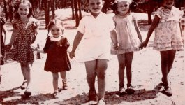 A row of five children holding hands pose for a photograph.