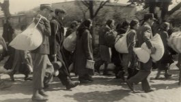 Photograph of Jewish police escorting a group of Jews who have been rounded-up for deportation from the Łódź ghetto on June 25, 1944.