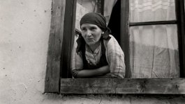 A woman wearing a scarf on her head leans out of a window. Photo taken circa 1935-1938.