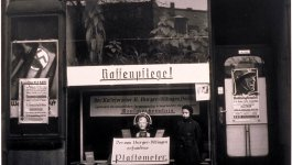 A girl stands by a store's window display showing a skull measuring device on mannequin's head. Circa 1933.