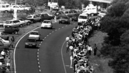 Long line of hundreds of South Africans along a busy highway.