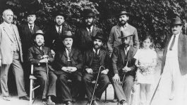 Group photo of men in suits and a young girl.