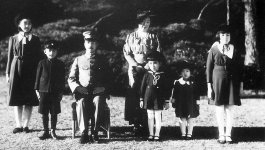 Photo of the Japanese Imperial Family. One man seated in the foreground with five children. and a woman standing in the background.