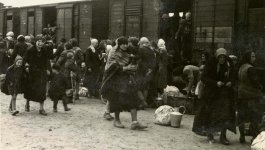 People and belongings outside a train having just arrived at Birkenau.