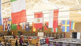 A school library with flags of many nations hanging from the ceiling.