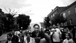 A crowd of people gather in a street to mourn the death of Eternity Gaddy. One man in the foreground holds a portrait of her.