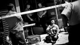A sobbing woman sits on a sidewalk in front of a store, as police officers stand around the storefront.