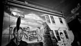 The exterior wall of a building features two murals, featuring portraits of young victims of violence.