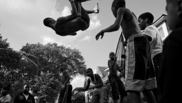 A group of children jump together on a trampoline. One child in the center does a back flip.