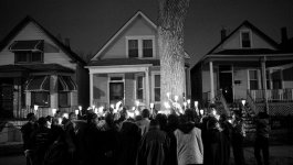 Fifty people holding candles gather for a nighttime vigil for Albert Vaughn.