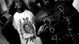 "Two young men wear shirts memorializing their friend, Darius Mitchell. One shirt says ""RIP D'Man"" and the dates ""1992-2007"" along with a portrait. The other shirt has the numbers ""065"" and ""064"" and the text ""D'ville"""