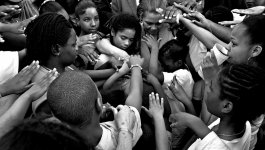 A group of people huddle together and place their hands on one another to pray for a victim of urban violence.