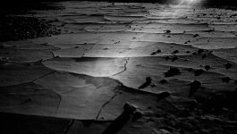Black and white photo of the sun shining across the cracked and rocky soil of the Badlands.