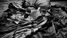 A young boy sleeps on a bed, covered in a quilt and laying on top of a wolf blanket. On the ground next to the bed is another set of rumpled bedding.