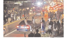 Newspaper front page featuring a photo of nighttime demonstrations in Ferguson.