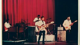 Booker T and the MGs performing on a stage with a red curtain in the background.