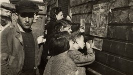 Photograph of a crowd reading an announcement about food rations tacked to a wall in the Łódź ghetto and copying down the information.