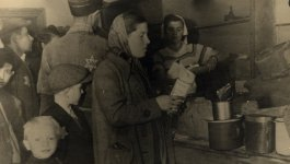 Photograph of Feiga Grosman Fraytag and her son Jakub standing in line to collect their food rations in the Łódź ghetto.
