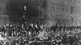 A large crowd of Germans gather in the streets of Berlin, with Nazi flags displayed, to take an oath of loyalty to Adolf Hitler. Dated February 25, 1934.