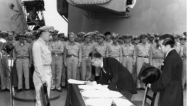 General Douglas MacArthur observes as Japanese Foreign Minister Shigemitsu Mamoru signs the Instrument of Surrender.