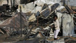 Black South African child pushes a trolley among trash and rubble.