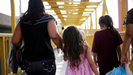 Two adult women and two young girls holding hands and walking across a yellow bridge.