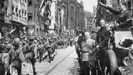 Children of the Hitler Youth march down a street in 1933, while their leader, Baldur von Schirach, salutes them.