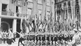 Young men and boys marching and saluting Adolf Hitler. Swastika banners on building in background.