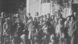 A large group of children of varying ages gather for a group photo outside a building.