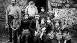 A family of four adults and seven children sitting and standing in front of the doorway of a building.