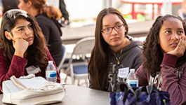 Three students sitting at a table and listening to a speaker.