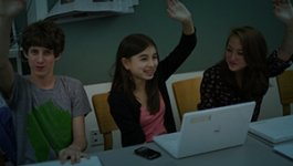 group of students raising hands with laptop on table