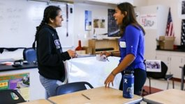 A female teacher in a blue shirt in conversation with her female student wearing a sweatshirt.