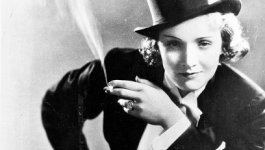 Black and white photo of a woman in a tuxedo and top hat with a cigarette in her mouth.