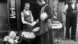A woman at the marketplace exchanges a large basket of banknotes for a cabbage.