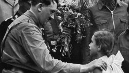Adolf Hitler has his hand placed on the soldier of a young girl in a white dress.