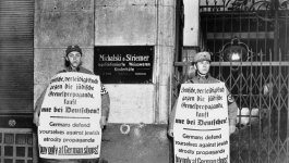 Two men in SA uniforms hold large signs with German writing.