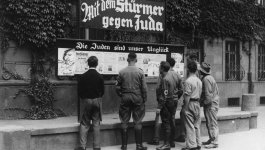 A group of men, two with visible swastika arm bands, read a bulletin of propaganda.