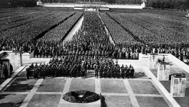 Movie still from the Triumph of the Will. Shows crowds of Nazi soldiers and civilians gathered in neat, orderly lines.