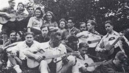 Young men and women sit together on a rock. Some of them are holding guitars.
