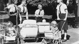 Four girls in uniforms push baby carriages.