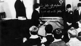 Boys stand in front of the class around a chalkboard on which a Jewish star is drawn.
