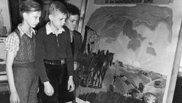 School boys look at a large painting, a Nazi flag in the background.