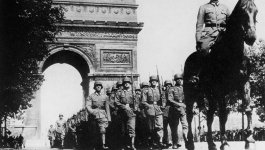 Troops on horses ride past the Arc de Triomphe in Paris, circa 1940.