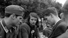 Two young men and a young woman conversing.