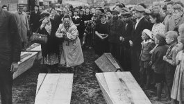 People gathered around two caskets. A woman in the front is crying.